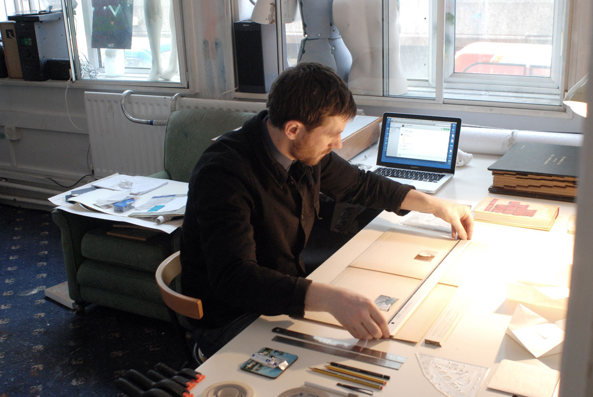 A man works on some papers at a desk in front of some large, bright windows.
