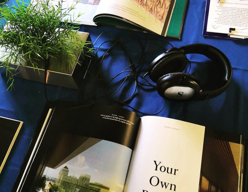 A tabletop covered with luxury magazines, and a pair of headphones