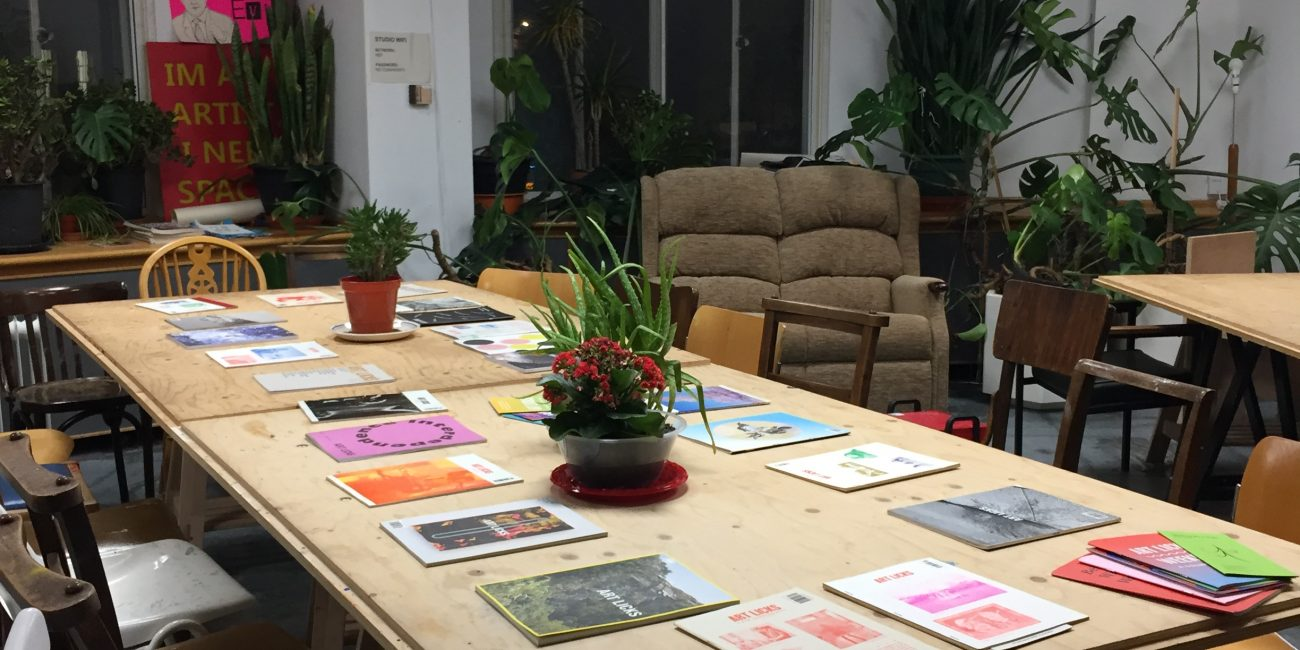 A large table with a series of Art Licks magazines laid out at intervals. The space is painted white with lots of big plants in