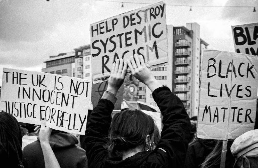 Black and white photo taken from within a protest crowd. Three people hold hand-written signs above their heads. They read [THE UK IS NOT INNOCENT, JUSTICE FOR BELLY], [HELP DESTROY SYSTEMIC RACISM] and [BLACK LIVES MATTER].