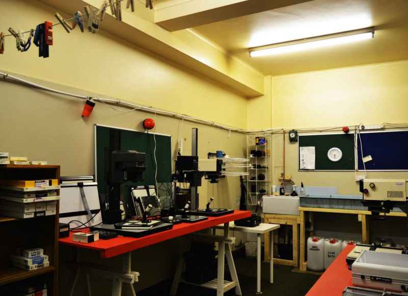 A brightly-lit room filled with photographic equipment. To illustrate the facilities available for photo development.