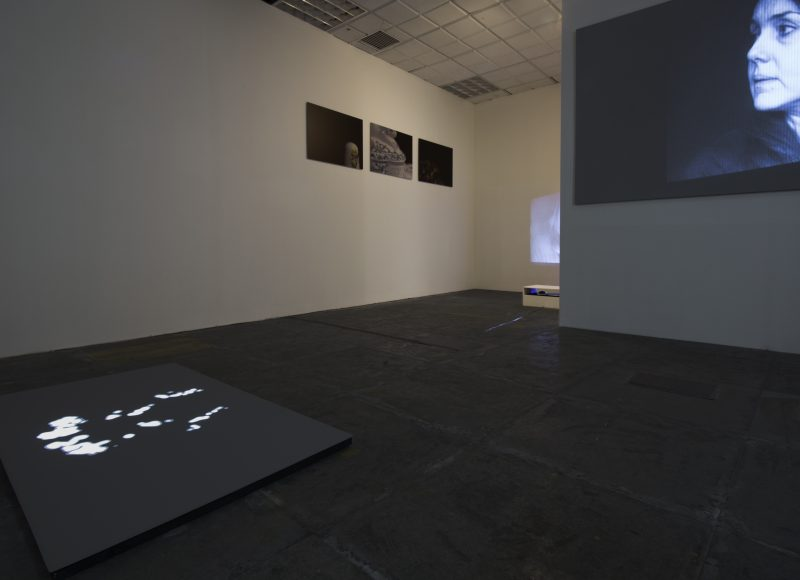 A white-walled gallery space, with illuminated pictures on two walls and the floor.