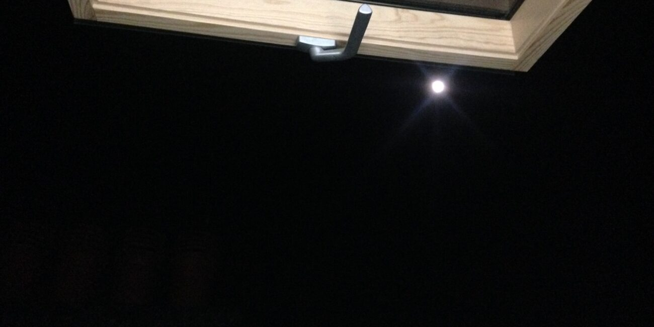 Black night sky with an open wooden window with a silver handle above the moon.
