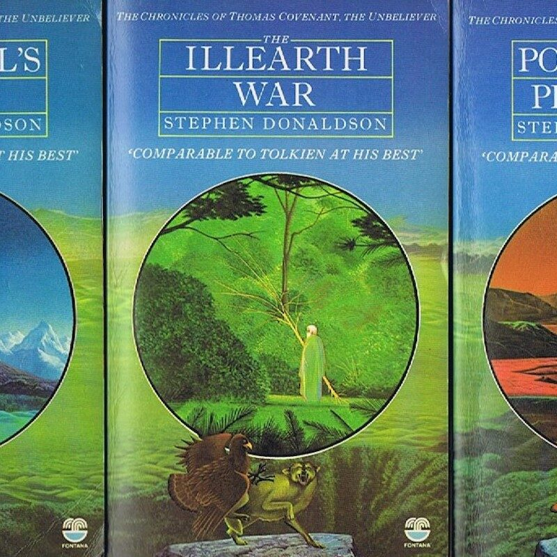 Photo of a series of 3 books in a row. The book taking up the majority of the image is has white writing over 2 images of mythical illustrations on its cover. The writing says 'The Illearth War, Stephen Donaldson' ' Comparable to Tolkein at his best'. The central illustration is framed in a circle and is of a person in a green cloak stood in. Forrest scene. The surrounding image is of 2 mythical creatures fighting on a stone informs of a green landscape and blue sky.