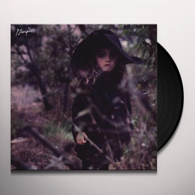 Vinyl cover with the disc half slid out . The cover image is a darkened photo of a child half submerged behind some trees. They have bold dark eye makeup and long blonde curly hair. They're wearing a large black floppy hat and a black polo neck jumper dress.