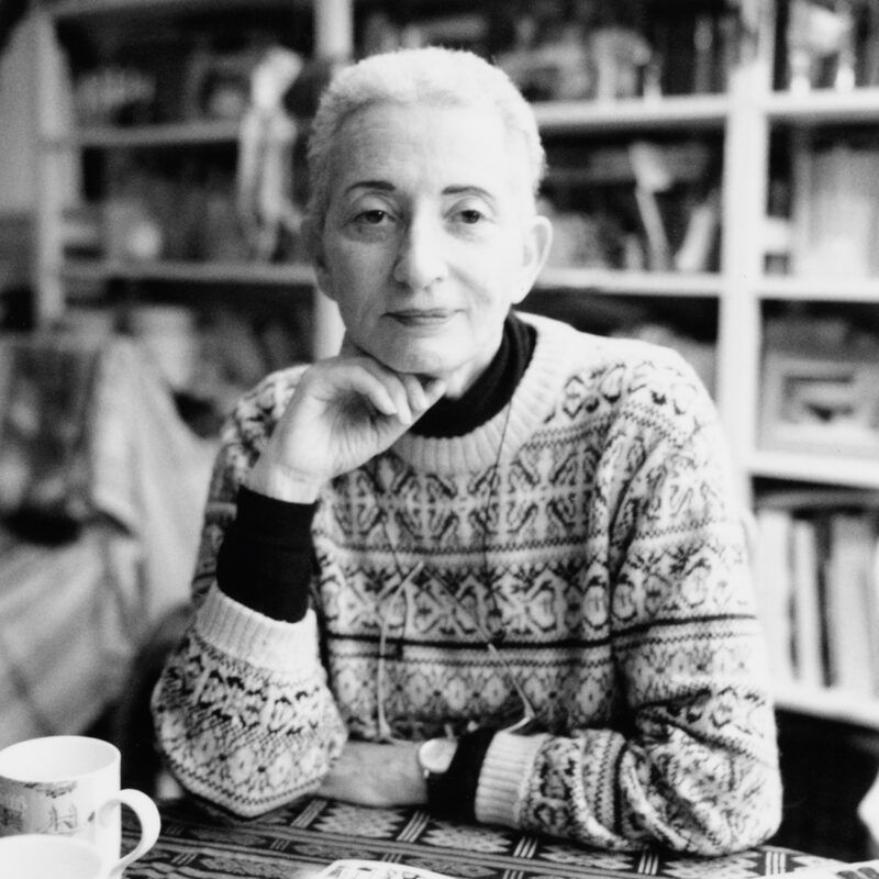 Black and White photo of a person smiling slightly looking just past the camera. They're sat at a table with a mug in front of an out of focus bookcase. They're resting their hand under their face and have short white hair. They're wearing a patterned cream jumper over a black top and have glasses round their neck.