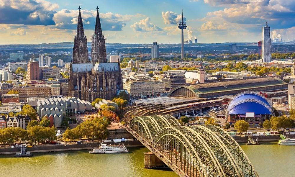 Photo of a city. There's a train station with a bridge going over the river. There's also a cathedral and trees and contemporary buildings in the foreground and background. The colours have been heightened and the sky is cloudy.