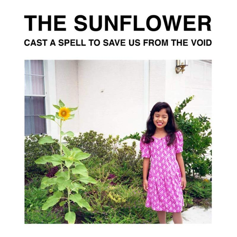 Black writing on a white background saying 'The Sunflower, cast a spell to save us from the void'. Underneath is a photo of a child in a pink dress smiling at the camera stood next to a sunflower. Behind is more greenery and a beige wall with a window.