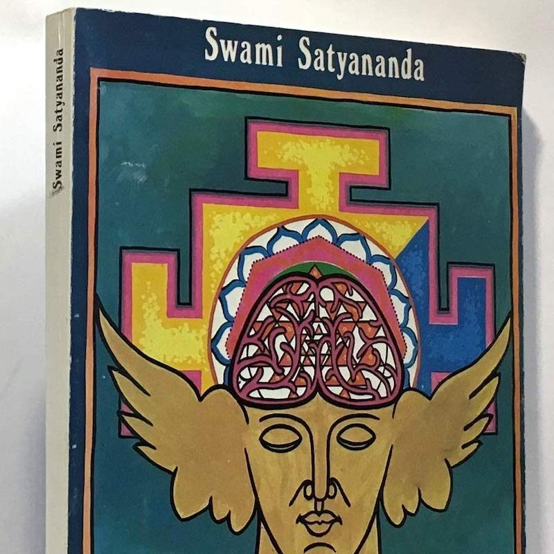 Photograph of the top a book. There's a dark blue banner with white writing that says 'Swami Satyananda'. In the centre is an illustration of a beige face with wings. On it's head is a geometric abstract pattern which grows out to fill the centre of the book cover.