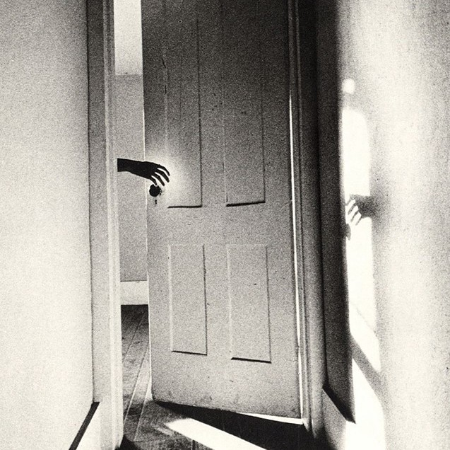Black and white hazy photograph of a hand emerging through an open door. The shadow of the hand is reflected in the sunlight on the wall opposite. It is a plain walled corridor with wooden walls.