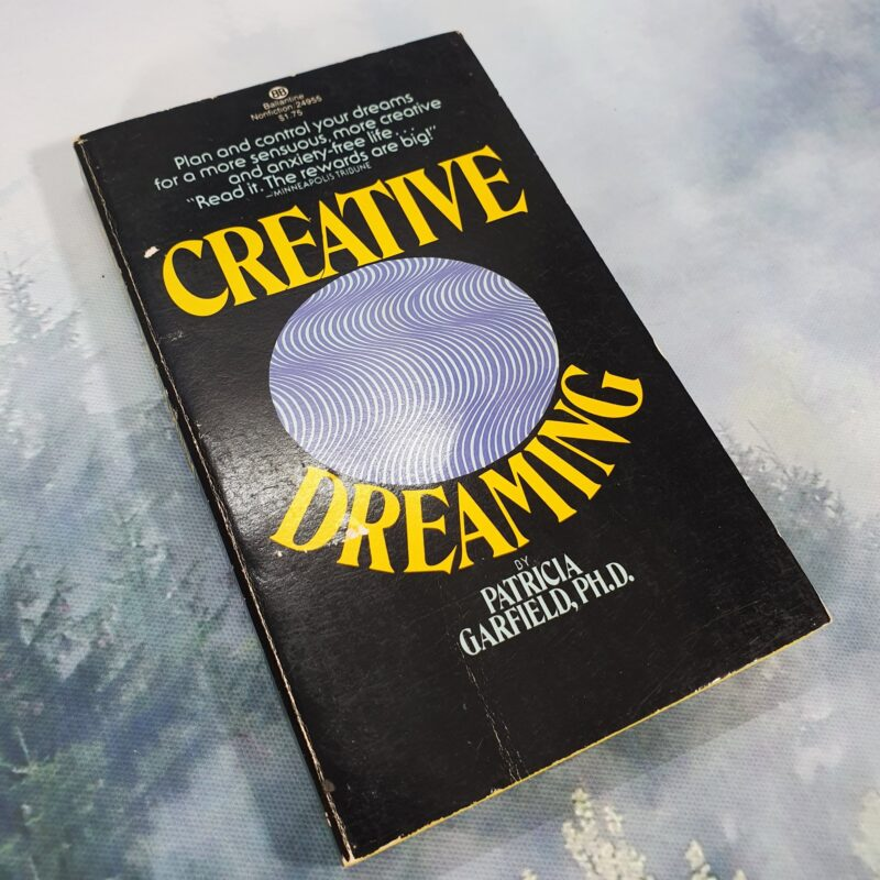 Photo of the book 'Creative Dreaming' by 'Patricia Garfield, PH.D' the tag line at the top of the cover says 'Plan and control your dreams for a more sensuous more creative and anxiety free life' 'read it the rewards are big'. The book has a solid black cover with a bold yellow title wrapped around a white circle with vertical wavy blue lines.