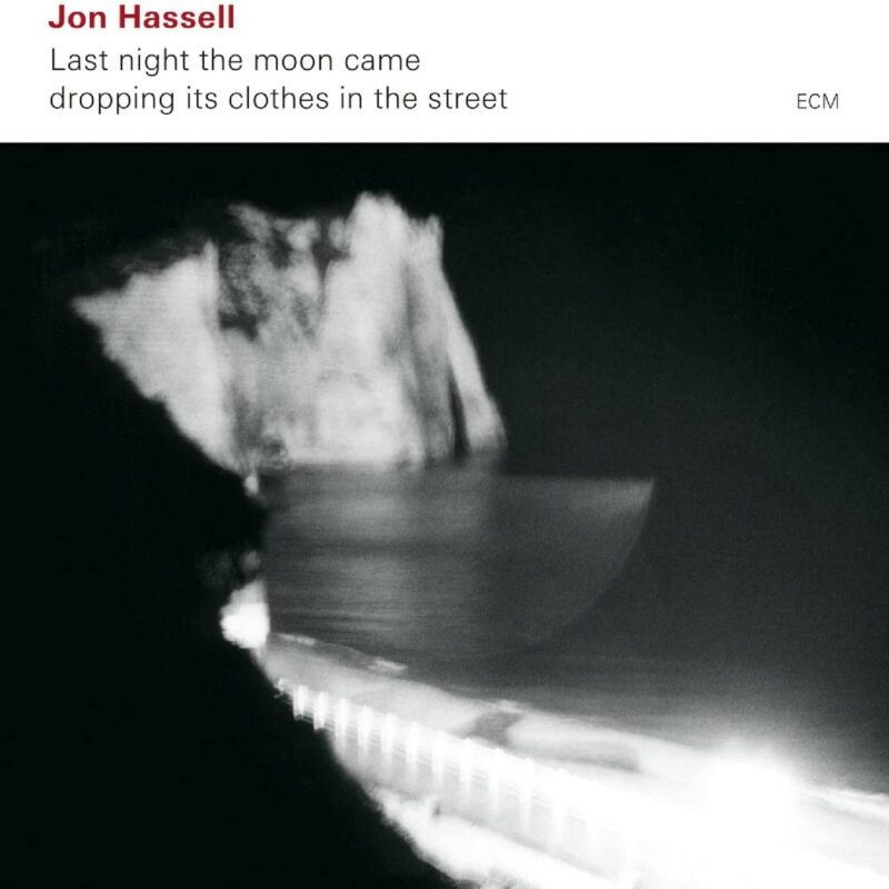 Black and white abstract image with some text above which is black and dark red on a white background. The text reads 'Jon Hassell, Last night the moon came, dropping its clothes in the street'.