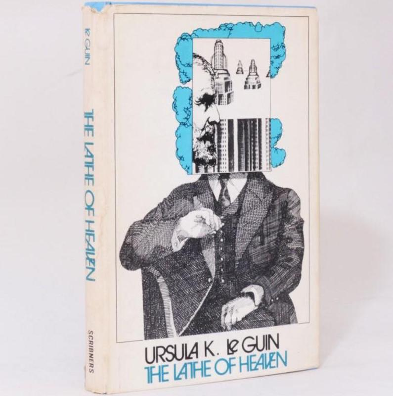 Photo of a copy of the book 'The Lathe of Heaven'. The image of the cover us a drawing of a person sat on a chair in a suit. Overlaid where the head would be is a profile of a bearded face with some segments of tower blocks. Behind this is a blue cloud.