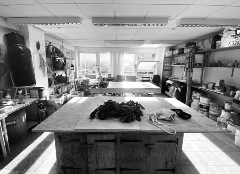 Black and white image of a ceramic studio, with 2 large desks in the centre of the room, and shelves containing ceramic vases and plates.