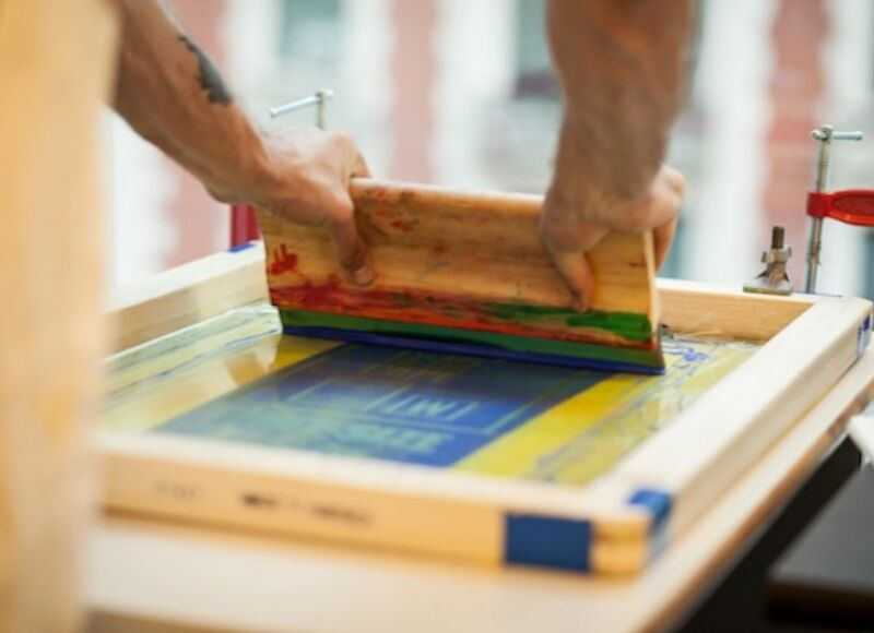 Image of two hands pulling a wooden squeegee across a screen to print in blue